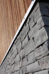 Rustikk grunnmurselementer og tettvokst børstet gran kledning
